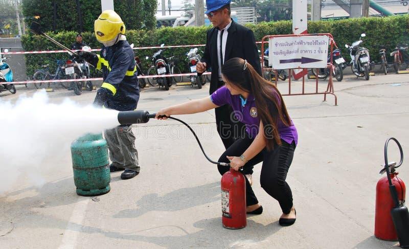 实践消防训练的人们灭火与粉末类型灭火器的  库存照片