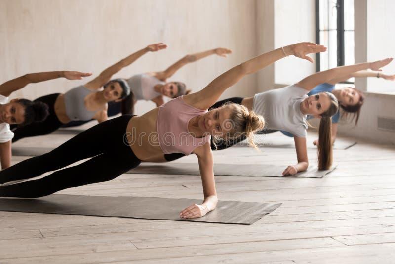 实践瑜伽教训,旁边板条锻炼的小组妇女 免版税库存照片