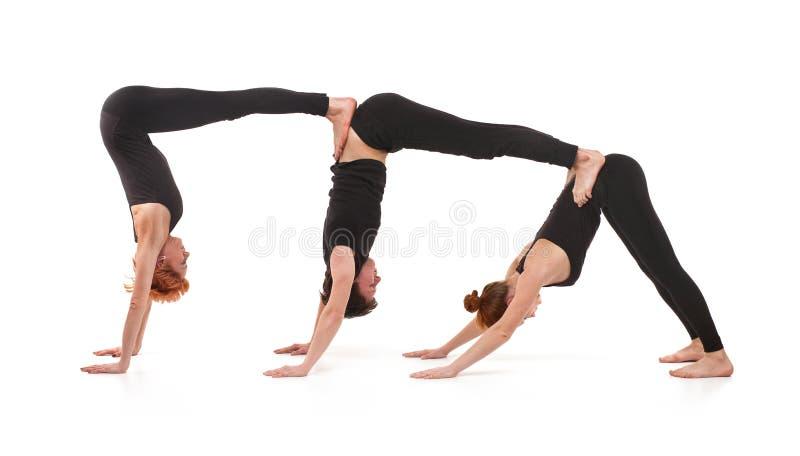 实践瑜伽的两个妇女和一人 免版税库存图片