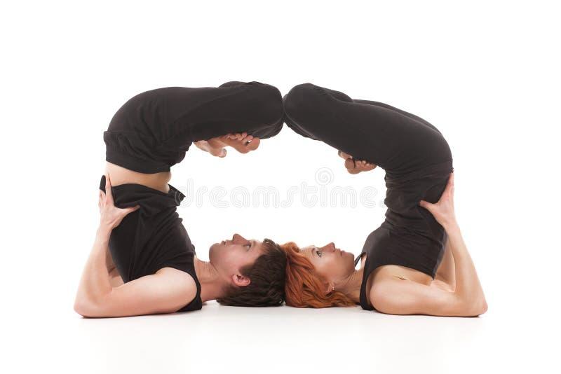 实践瑜伽的两个妇女和一人 库存照片