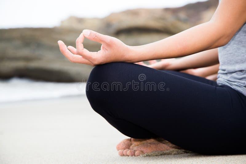 实践瑜伽的两名美丽的妇女在海滩 图库摄影