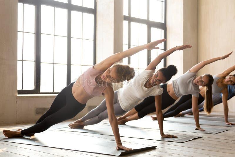 实践瑜伽的小组年轻运动的妇女,做Vasisthasana 免版税库存图片