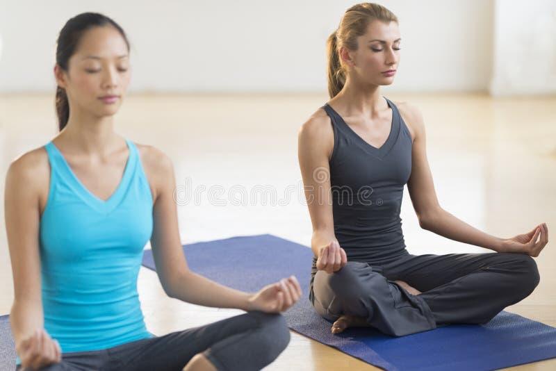 实践瑜伽的美丽的妇女在健身俱乐部 免版税库存图片