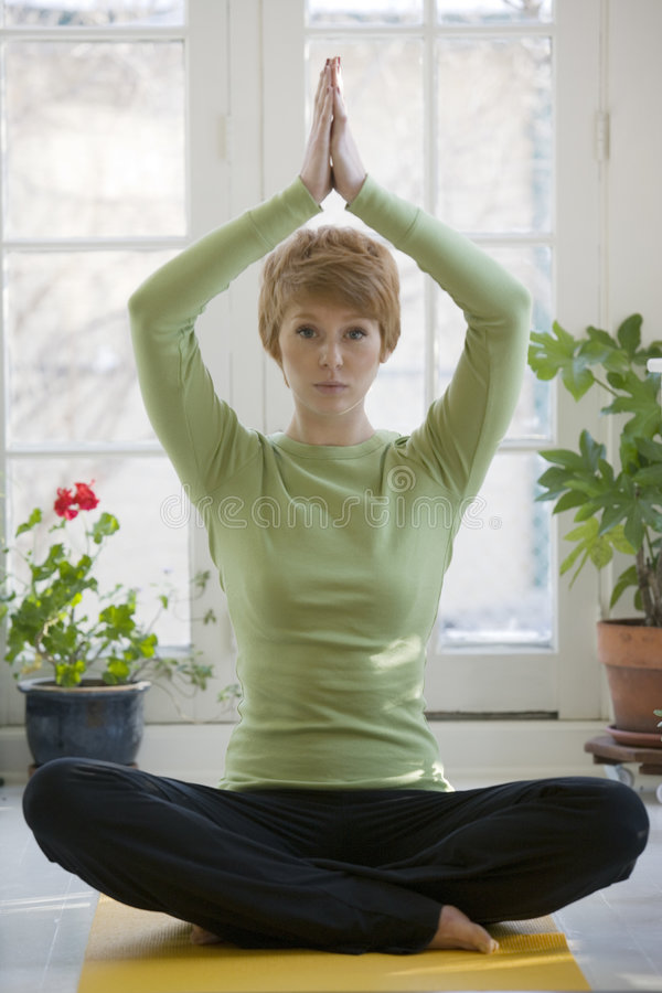 实践的俏丽的女子瑜伽年轻人 免版税库存图片