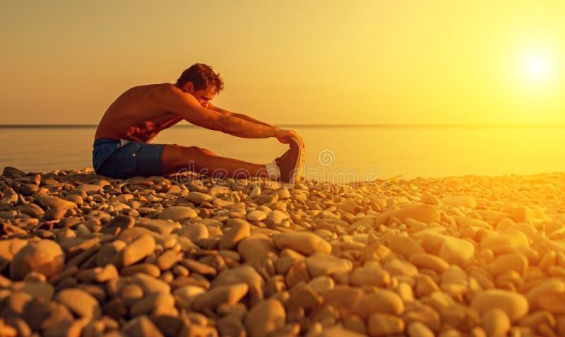 实践的运动员,在海滩的瑜伽在日落 免版税库存图片