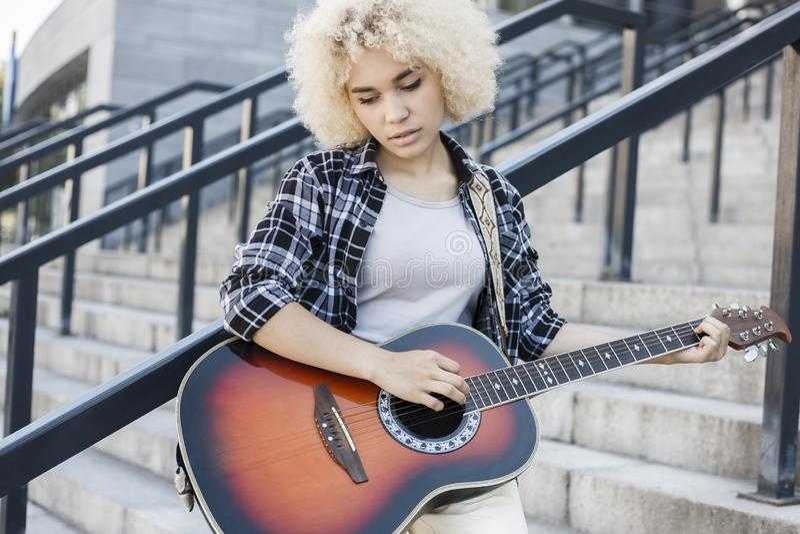 实践美丽的沉思的女孩弹吉他户外 库存照片