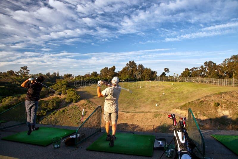 实践他们的高尔夫球的两个人摇摆在开车范围 免版税库存图片