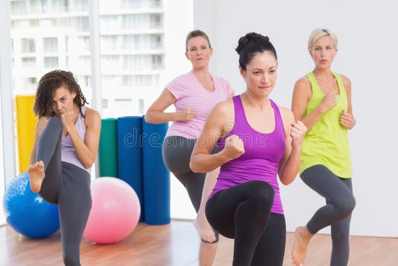 实践kickboxing的妇女在健身演播室 免版税库存照片