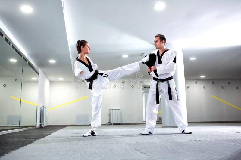 实际上实践跆拳道的体育的挑战年轻女人 免版税库存图片