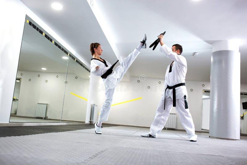 实际上实践高反撞力的跆拳道的挑战年轻女人 免版税库存照片
