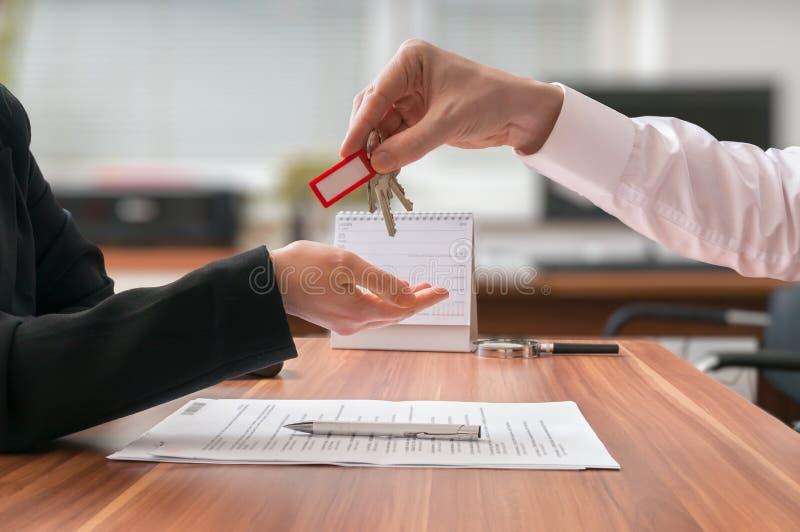 实际概念的庄园 地产商通过钥匙给坐在书桌后的客户 免版税库存照片