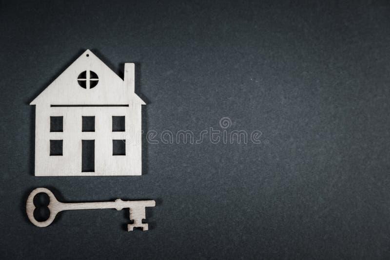 实际概念的庄园 小有钥匙的玩具木房子在灰色背景 免版税库存照片