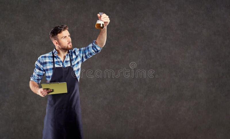 实验员酿酒者酿酒商检查在t的液体 免版税库存图片