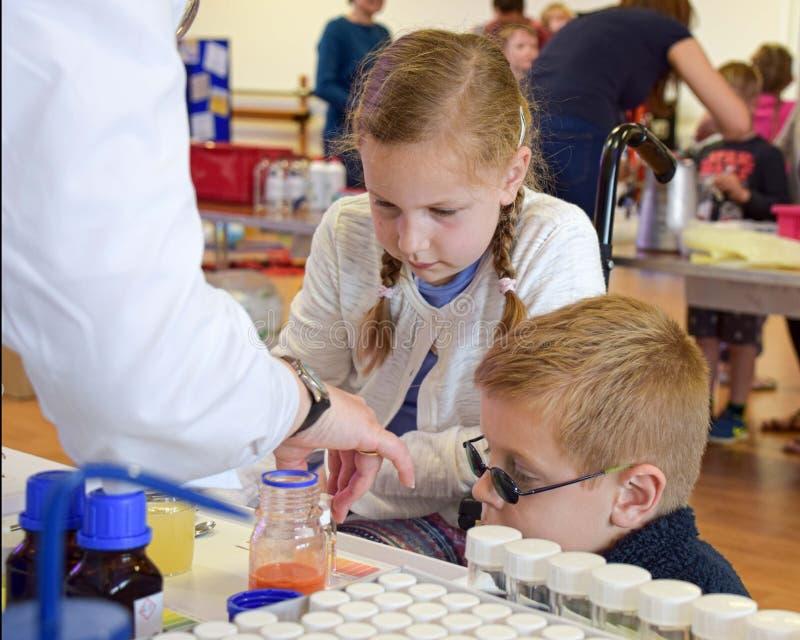 实验室化学家达每在教关于化学作为英国词根一部分,科学,技术,引擎的孩子的实验室外面的天 库存图片