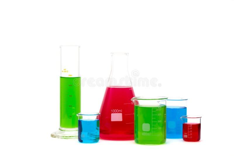 实验室玻璃器皿充满五颜六色的液体 查出在白色 免版税库存图片