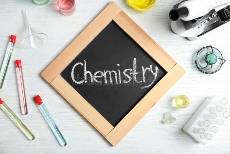 实验室玻璃器皿和板与词化学在木背景 免版税库存图片