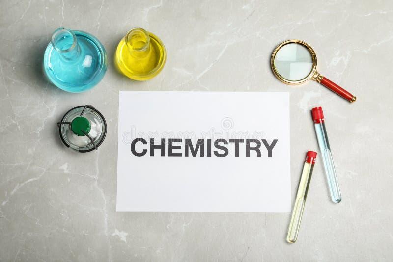 实验室玻璃器皿和纸与词化学在灰色背景 免版税库存照片