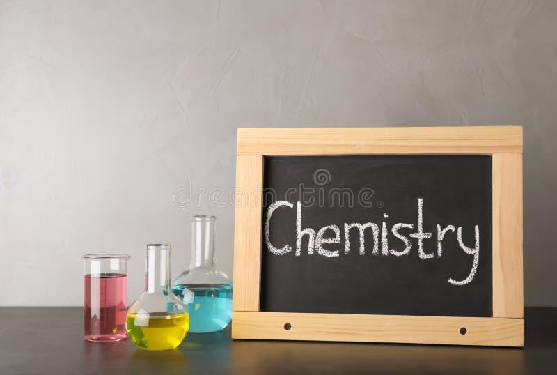 实验室玻璃器皿和黑板有词的化学在桌上反对灰色背景 库存图片