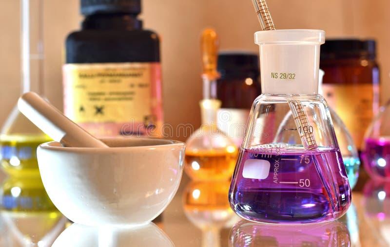 实验室玻璃器皿用五颜六色的解答和化学制品在背景中 库存照片