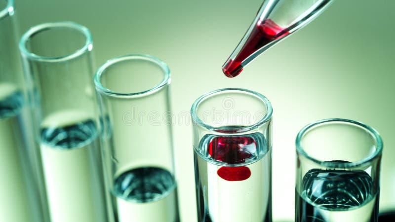 实验室设备,在试管投下红色液体 免版税库存照片