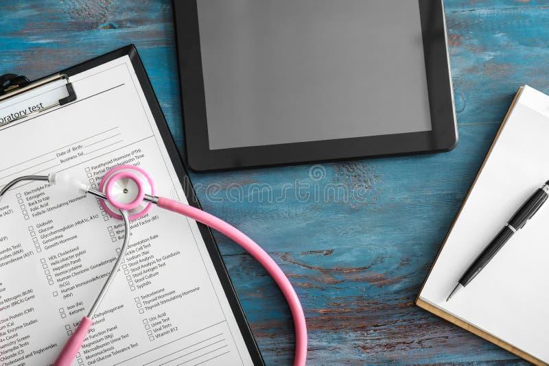 实验室试验与听诊器的请求在桌上的形式和平板电脑 r 免版税库存照片