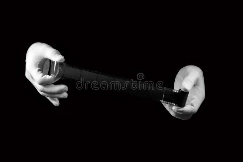 实验室,在白色手套的手拿着一部黑白影片 图库摄影