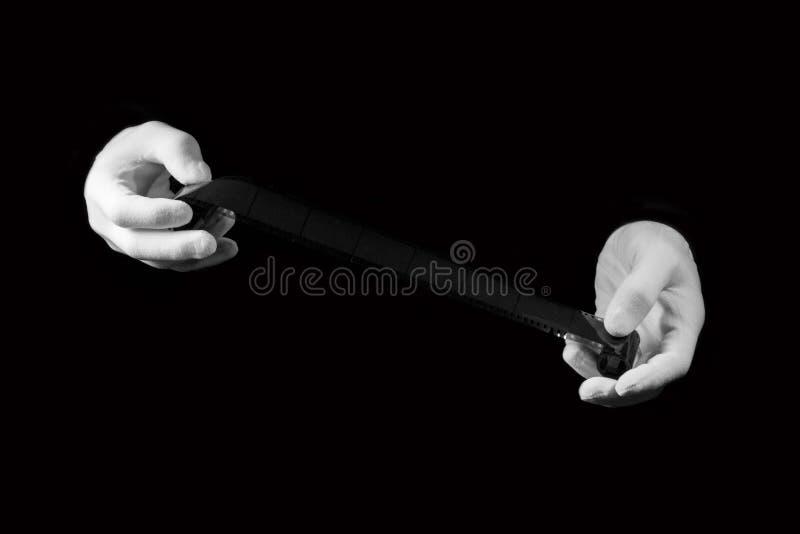 实验室,在白色手套的手拿着一部黑白影片 免版税库存图片