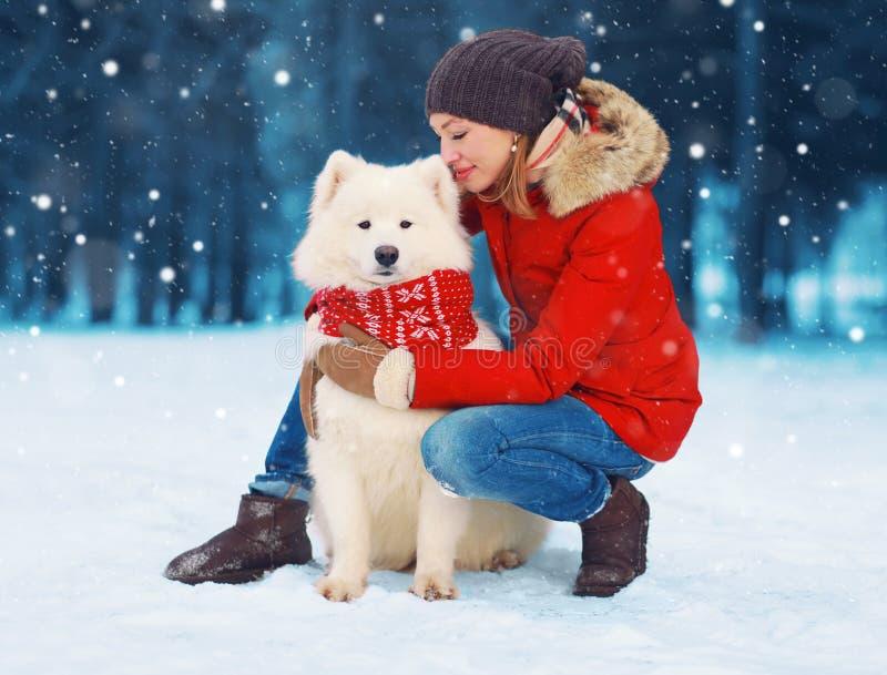 宠爱在雪的圣诞节愉快的少妇所有者拥抱白色萨莫耶特人狗在雪花的冬天 免版税图库摄影