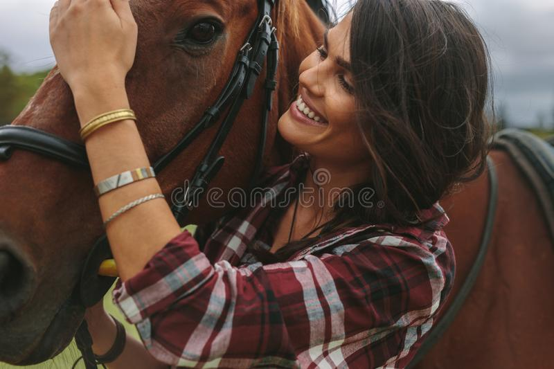 宠爱她的马的微笑的妇女 免版税库存图片