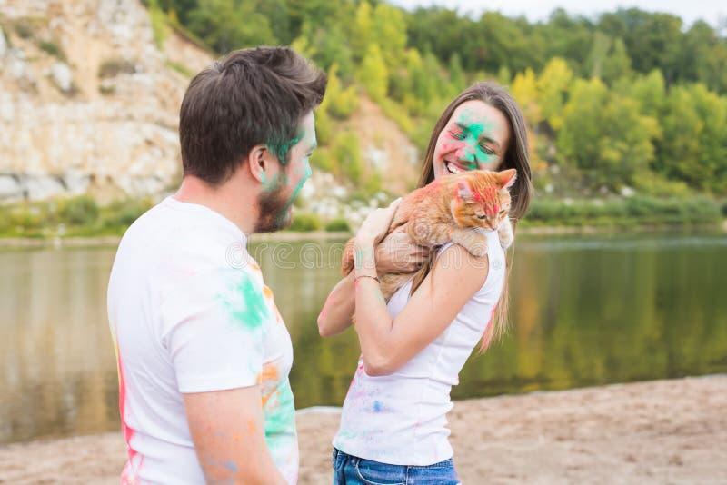 宠物、夏天旅游业、节日holi和自然概念-滑稽的男人和妇女有猫的在自然本底 免版税库存图片