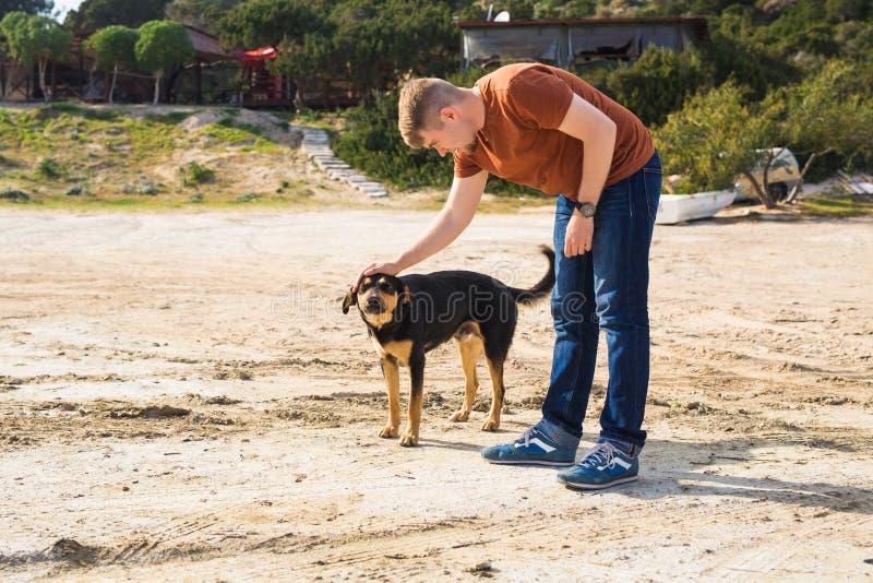 宠物、家畜、季节和人概念-有走他的狗的愉快的人户外 免版税库存图片