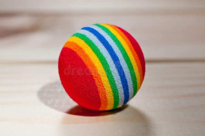 宠物的球红色与色的条纹,有弹性在木背景 库存照片