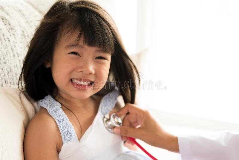 审查一个小女孩的医生通过使用听诊器 免版税图库摄影