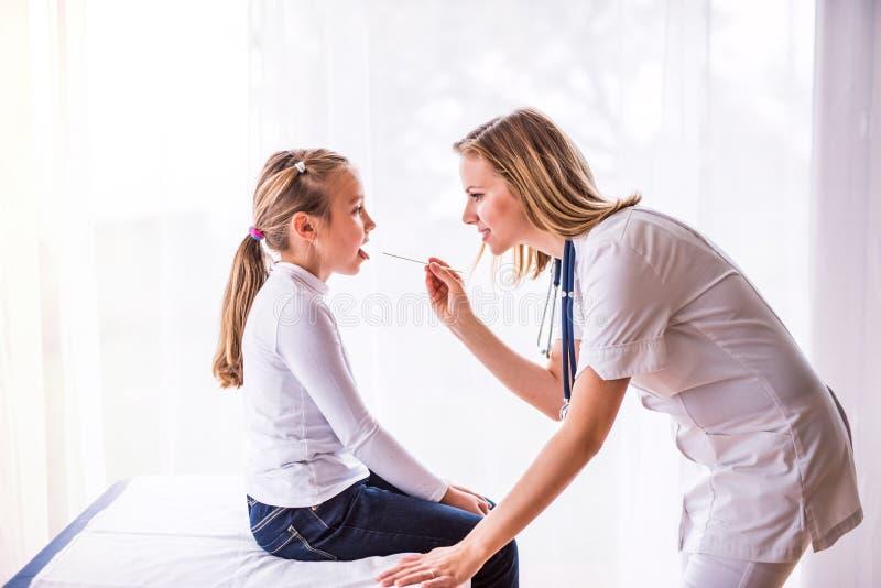 审查一个小女孩的年轻女性医生在她的办公室 图库摄影