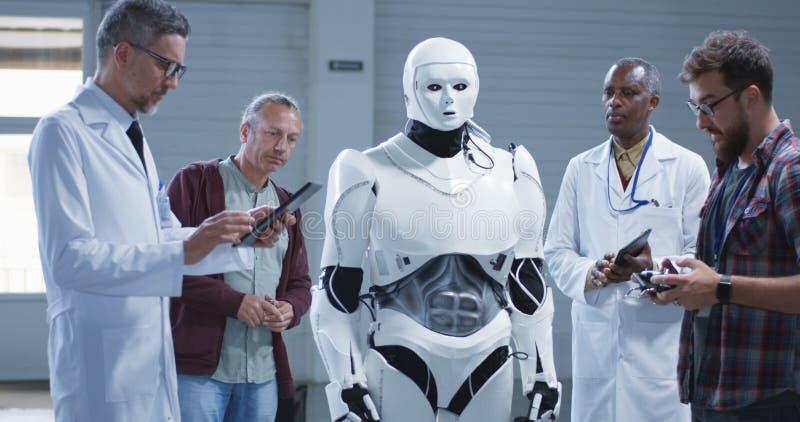审查一个有人的特点的机器人的科学家 免版税库存图片