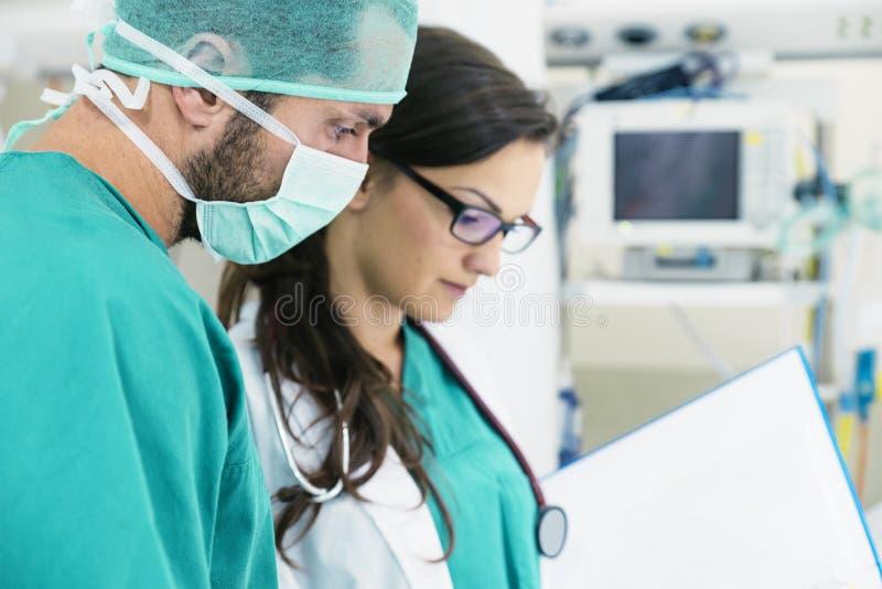 审查一个医疗报告的医疗队工作者 图库摄影