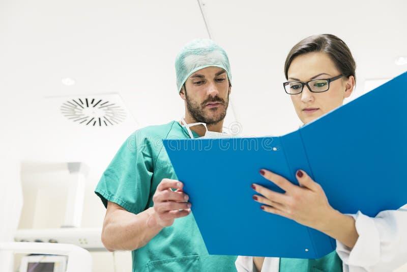 审查一个医疗报告的医疗队工作者 免版税库存照片