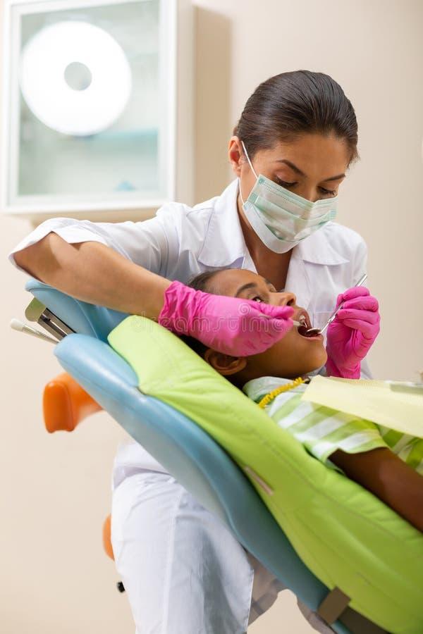审查一名年轻女性患者的严肃的深色头发的妇女牙医 库存照片