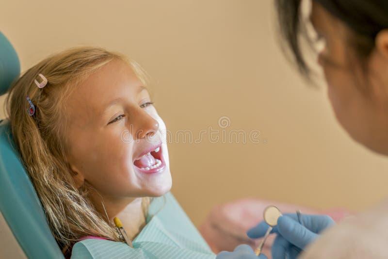 审查一点girl& x27的牙医; 在诊所的s牙 坐在椅子的小女孩在牙医附近在牙齿治疗以后 少许 免版税库存图片