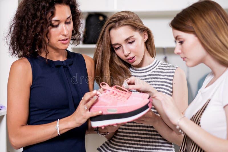 审查三个年轻的女朋友拿着体育鞋类站立在时尚陈列室里的新的对 库存照片