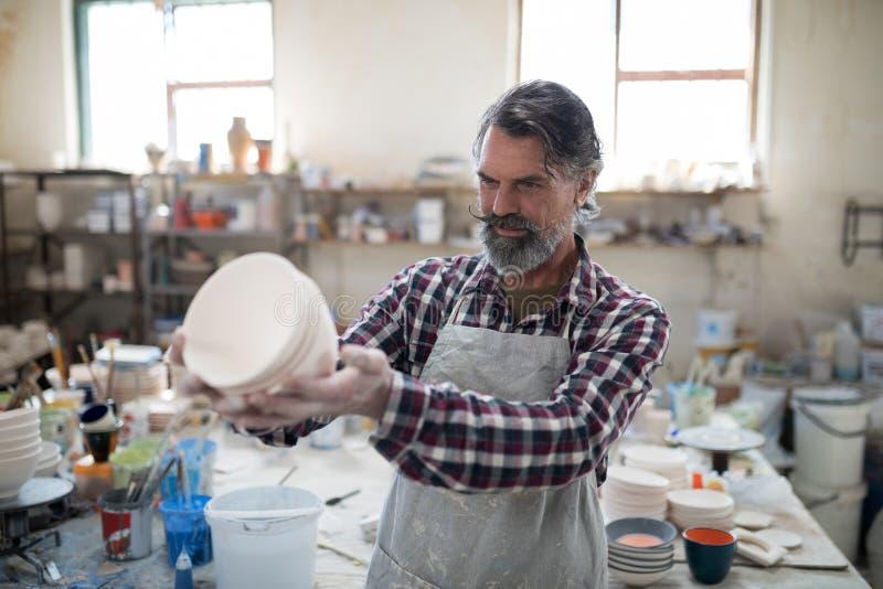 审查他的缺点的被聚焦的男性陶瓷工创作 图库摄影