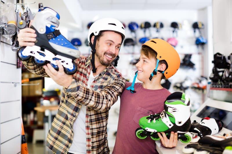 审查各种各样的路辗冰鞋的父亲和儿子 免版税库存照片