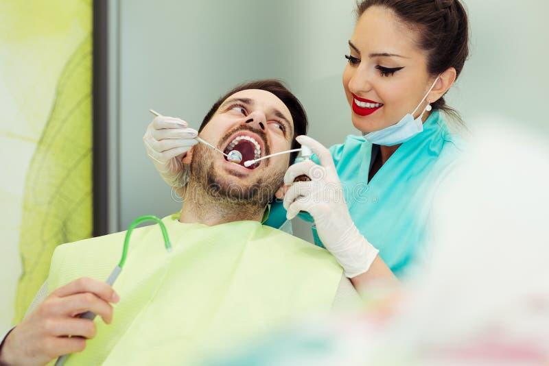 审查和工作在男性患者的女性牙医 免版税库存照片