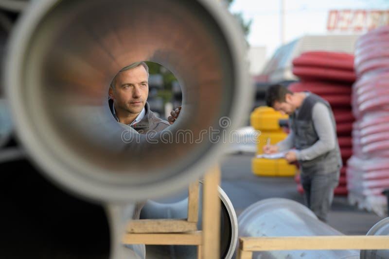 审查大管子的男性监督员在建造场所 免版税库存图片