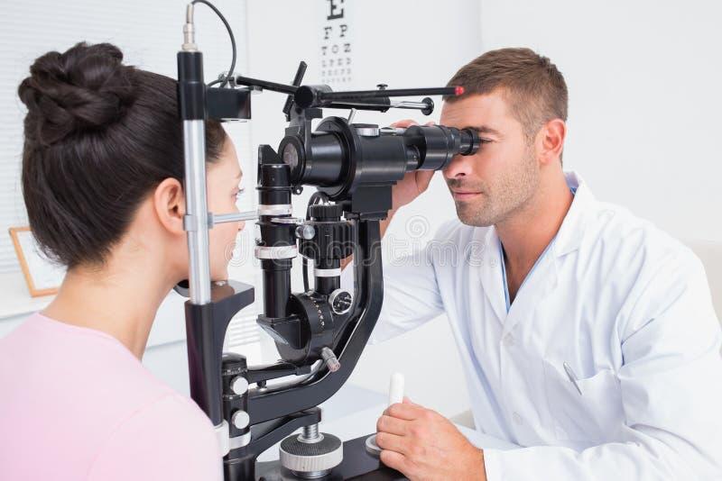 审查女性患者的眼镜师通过被切开的灯注视 图库摄影