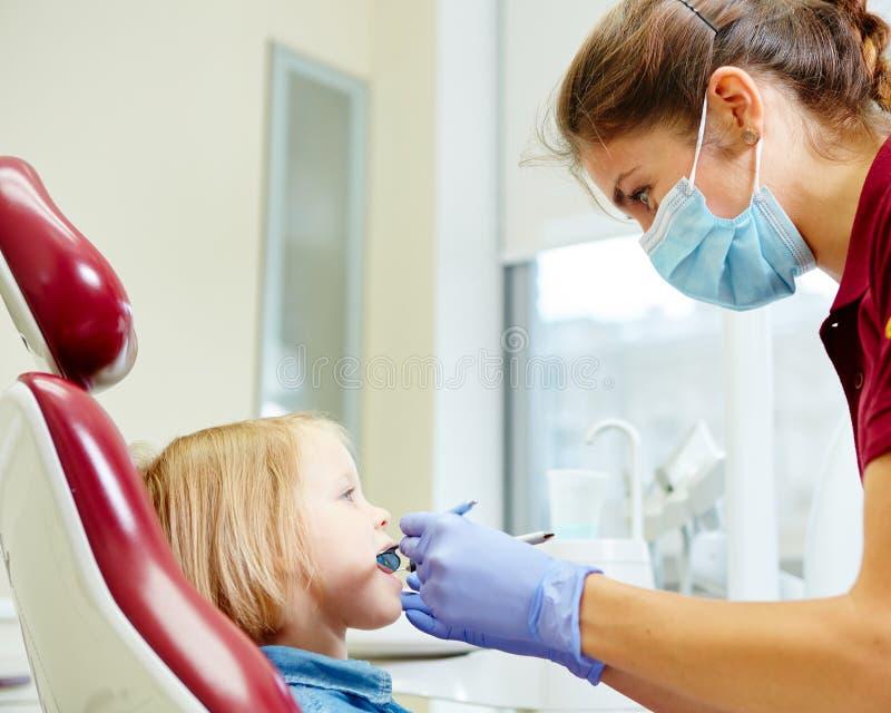 审查小女孩牙的小儿科牙医  免版税库存图片