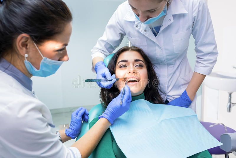 审查患者的牙齿医生 图库摄影