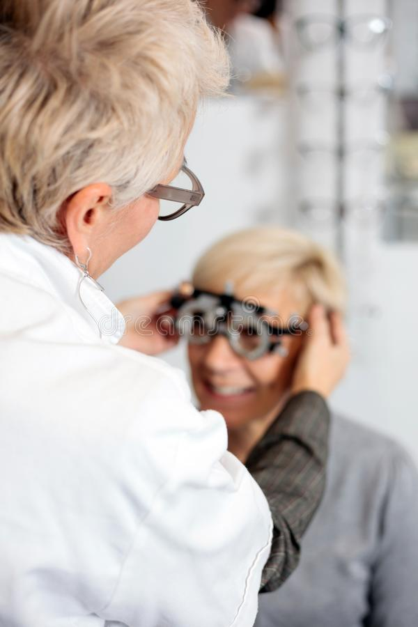 审查成熟妇女的女性眼科医生在眼科学诊所,确定屈光率 免版税图库摄影