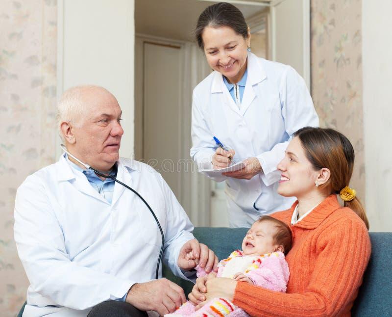 审查新出生的婴孩的儿科医生医生 免版税库存图片
