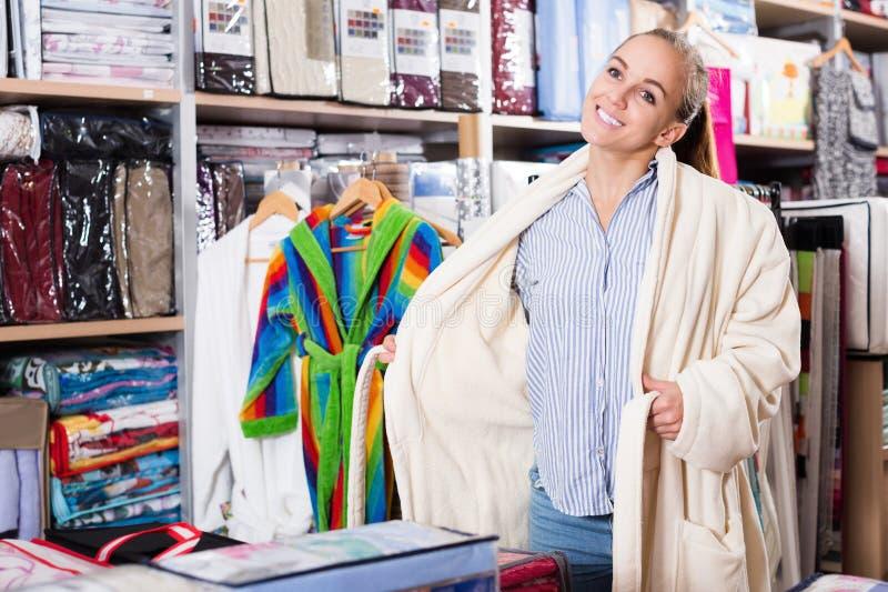 审查新的浴巾的顾客在纺织品商店 库存图片